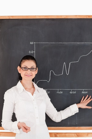 Dark-haired teacher explaining charts to students in a classroom photo