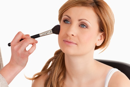 Make-up artist applying make up to a cute blond-haired woman in a studio Stock Photo - 10231998