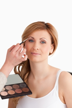 Make-up artist applying make up to a blond-haired female in a studio Stock Photo - 10231897