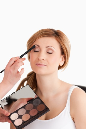 Make-up artist applying make up to a young woman in a studio Stock Photo - 10231902