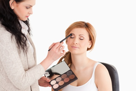 Young woman having her make up done by a make up artist in a studio photo