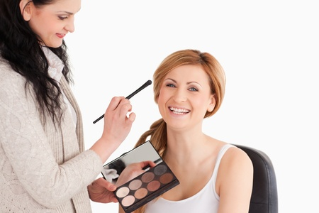 Attractive blond-haired woman having her make up done by a make up artist in a studio photo