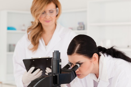 Dark-haired scientist and her assistant conducting an experiment in a lab photo