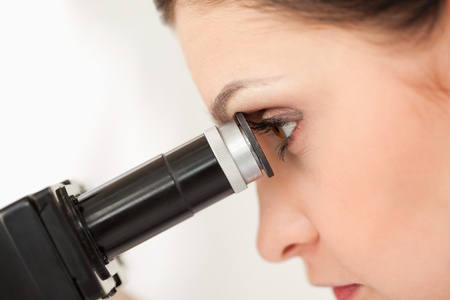 Dark-haired scientist looking through a microscope in a lab photo