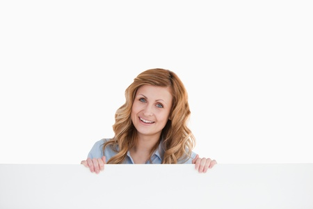 Lovely blond-haired woman standing behind an empty white board  photo