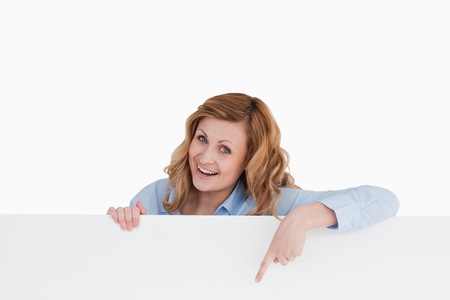 Happy blond-haired woman standing behind a white board while showing something Stock Photo - 10231639