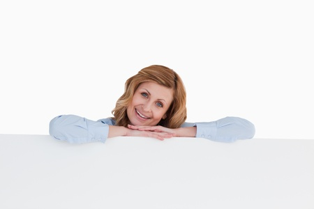 Smiling blond-haired woman standing behind a white board Stock Photo - 10231505