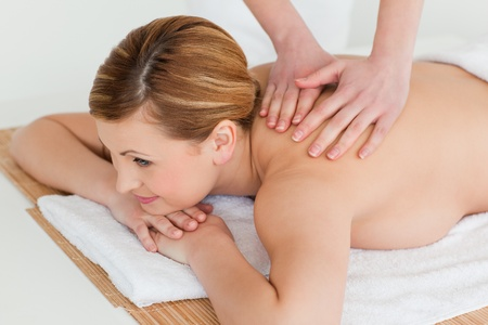 Cute blond-haired woman getting a massage in a spa centre photo