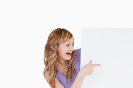 Attractive blond-haired woman holding a white board while showing something Stock Photo - 10231666