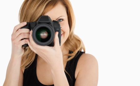 Cute blond-haired woman taking a photo with a camera on a white background photo