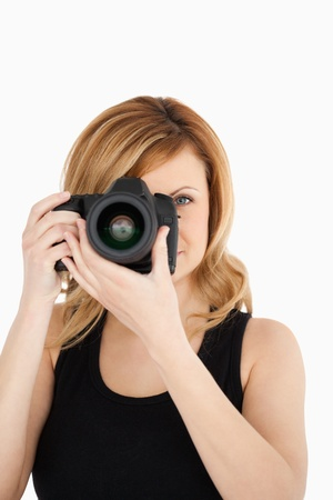 Attractive blond-haired woman taking a photo with a camera on a white background photo