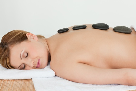 Pretty blond-haired woman lying down with stones on her back in a spa centre photo