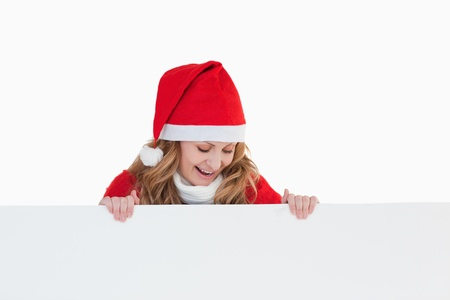 Happy blond-haired woman dressed as Santa Claus holding a white board photo