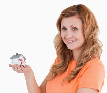 Cute woman holding an house model on a white background photo