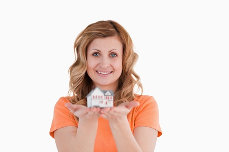 Smiling woman holding an house model on a white background photo