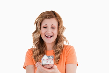 Happy woman holding an house model on a white background photo