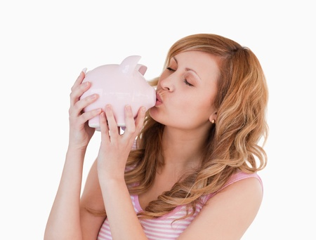 Blond-haired woman kissing her piggybank on a white background photo