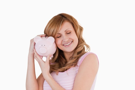 Cute woman happy with her piggybank on a white background Stock Photo - 10196468