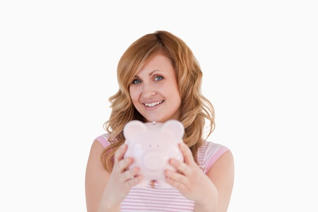 Cute woman posing while holding her piggybank on a white background photo