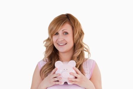 Attractive woman posing while holding her piggybank on a white background photo