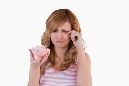 Blond-haired woman crying while holding her broken piggybank on a white background photo