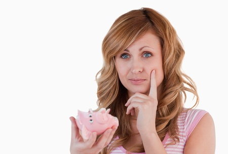 Blond-haired woman thoughtful while holding her broken piggybank on a white background photo