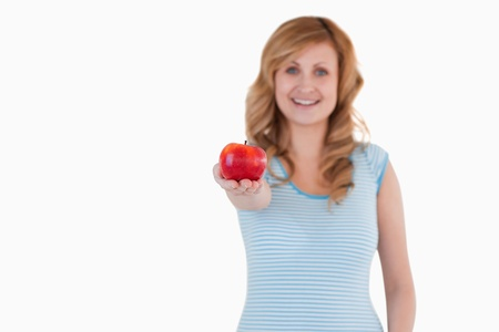 Cute woman showing a red apple to the camera on a white background photo