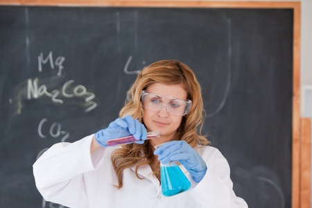 Young blond-haired woman carrying out an experiment in a laboratory Stock Photo - 10212704