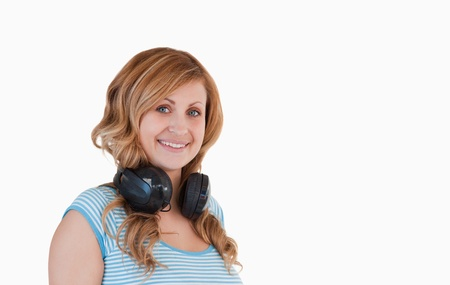 Attractive blond-haired woman posing with her headphones around her neck photo