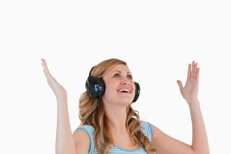 Cute blond-haired woman enjoying while listening to music and watching towards the sky Stock Photo - 10191700