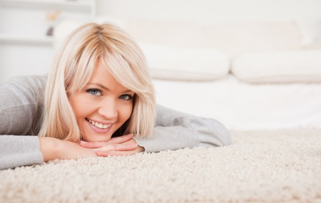 Charming blond woman posing lying down on a carpet in the living room Stock Photo - 10196602