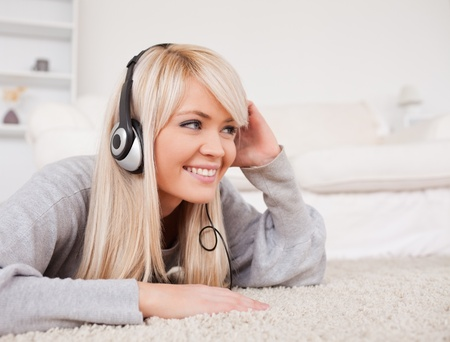 Attractive blond woman with headphones lying on a carpet in the living room photo