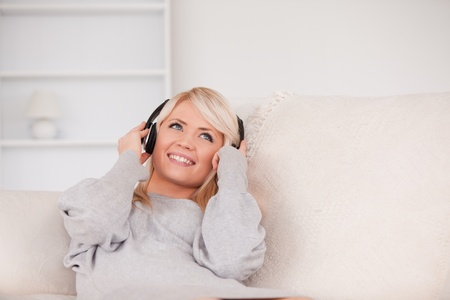 Attractive blond woman with headphones lying in a sofa in the living room photo