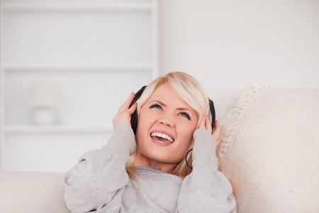Beautiful young blond woman with headphones lying in a sofa in the living room photo