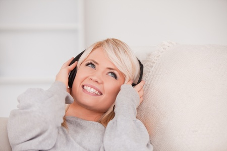Charming young blond woman with headphones lying in a sofa in the living room photo