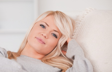 Portrait of a happy blonde woman lying on a sofa in her appartment photo