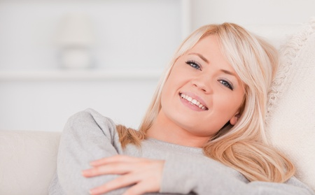 Portrait of a smiling blonde woman lying on a sofa in her appartment photo