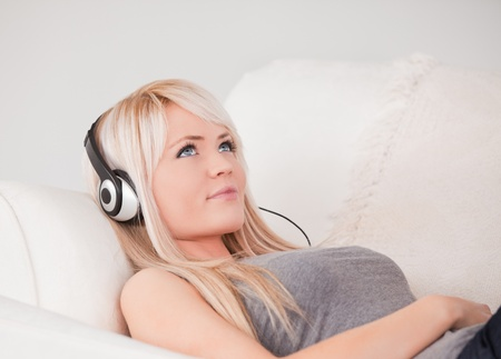 Attractive young blond woman with headphones lying in a sofa in a studio photo