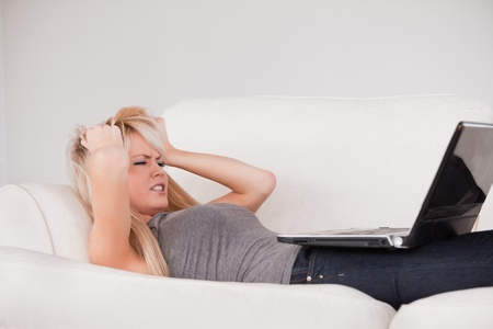 Attractive blond woman frustrated with her computer lying on a sofa in a studio photo