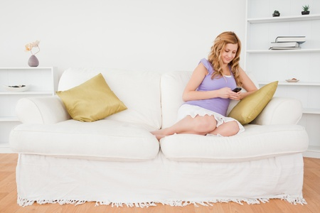 Beautiful red-haired woman writing a text message while sitting on a sofa in the living room photo