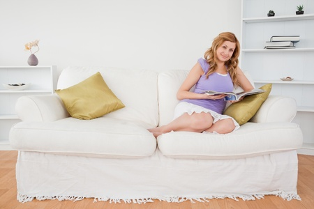Pretty red-haired woman reading a magazine and posing while sitting on a sofa in the living room Stock Photo - 10196566