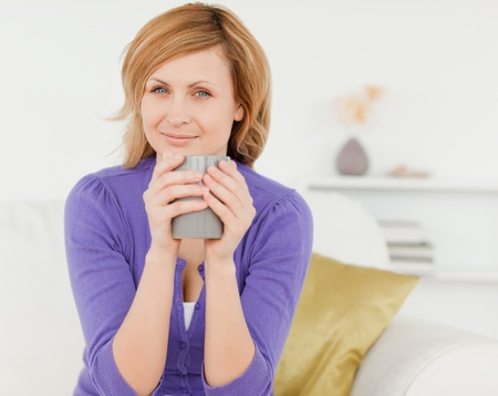 Charming red-haired woman holding a cup of coffee and posing while sitting on a sofa in the living room photo