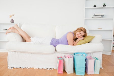Blond-haired woman lying on the couch having done her shopping photo