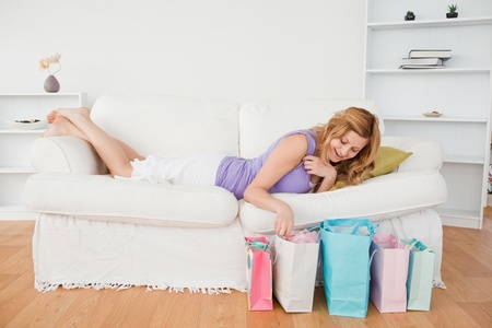 Cute blond-haired woman lying on the couch having done her shopping photo