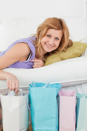 Pretty woman lying on the couch with her shopping bags in the living-room photo