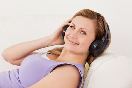 Beautiful blond-haired woman listening to music lying on the sofa in the living-room photo