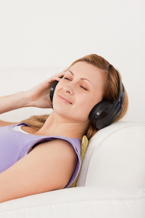 Happy blond-haired woman listening to music lying on the sofa in the living-room Stock Photo - 10196704