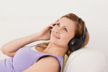 Smiling blond-haired woman listening to music lying on the sofa in the living-room photo