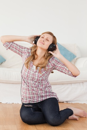 Happy woman listening to music while sitting on the floor in the living-room Stock Photo - 10205861