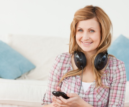 Attractive blond-haired woman with headphones and mp3 player sitting in the living-room photo